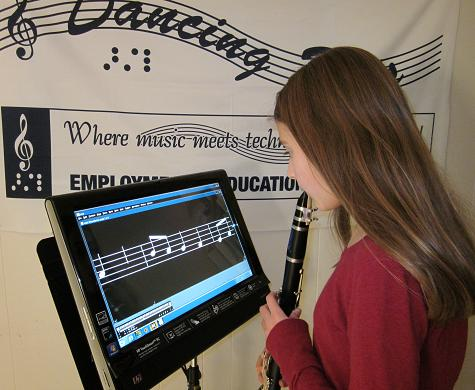 A girl plays her clarinet, reading the music enlarged on a computer screen mounted on a music stand.