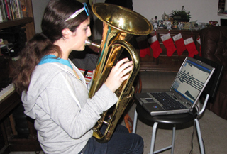 photo of girl playing the Euphonium in a living room, in front of a home-made music system.  All components can be seen, including the foot pedal.